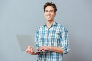 Laughing man standing with laptop computer over gray background and looking at camera stock vector