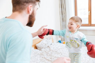 Father playing with his son in boxing gloves at home