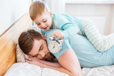 Little son holding alarm clock near sleeping father ear