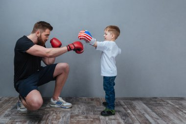 Father and little son working out in boxing gloves together