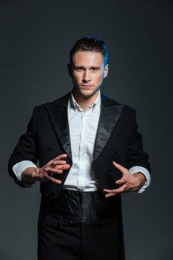 Man magician in balck tail coat conjuring tricks