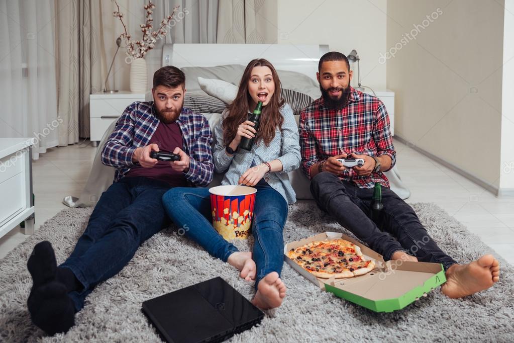 Juegos En Casa Con Amigos Sonrientes Amigos Comer Pizza Y Jugar A