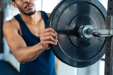 Healthy fitness man prepares to do excercises with a barbell