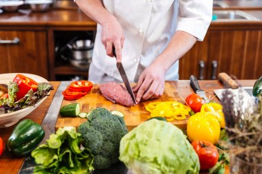 Professional chef cook cutting uncooked meat and fresh vegetables