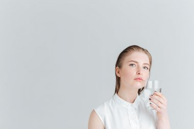 Pensive woman holding glass of water