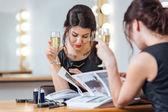 Hezká žena, pití šampaňského a čtení časopisu v šatně