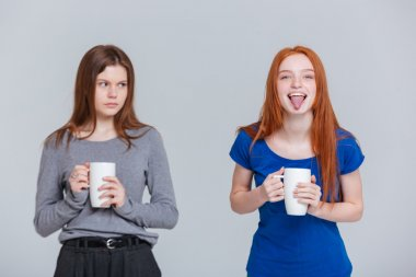 Two happy joking and sad frowning young women drinking tea