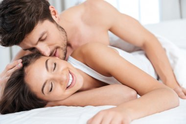 Close-up portrait of a couple kissing in bed