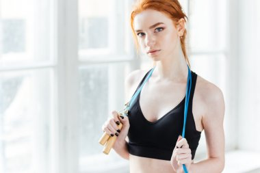 Attractive fitness girl holding skipping rope