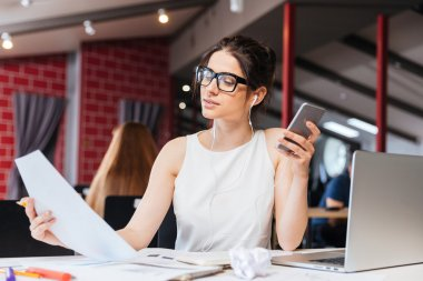 Businesswoman working and listening to music from smartphone in office