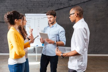 Group of confident people discussing new project in conference room