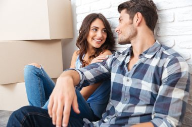 Happy couple sitting on floor around boxes after buying house