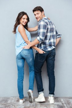 Couple standing backwards and looking at camera over gray background