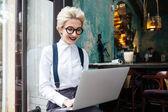 Fényképek Gyönyörű fiatal nő dolgozik a laptop, és mosolyogva szemüveg