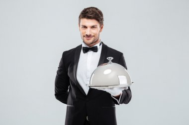 Smiling young butler holding tray with silver catering dome
