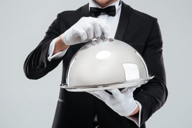 Serving tray with cloche holded by butlers hands in gloves