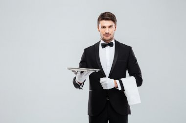 Attractive butler in tuxedo standing and holding silver empty tray