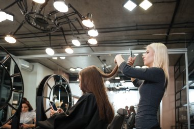 Woman getting haircut by female hairdresser at beauty salon