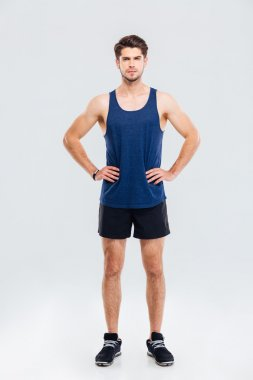 Full length portrait of sportsman standing with hands on hips