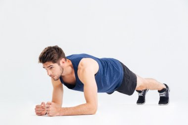 Focused handsome young sportsman doing plank core exercise