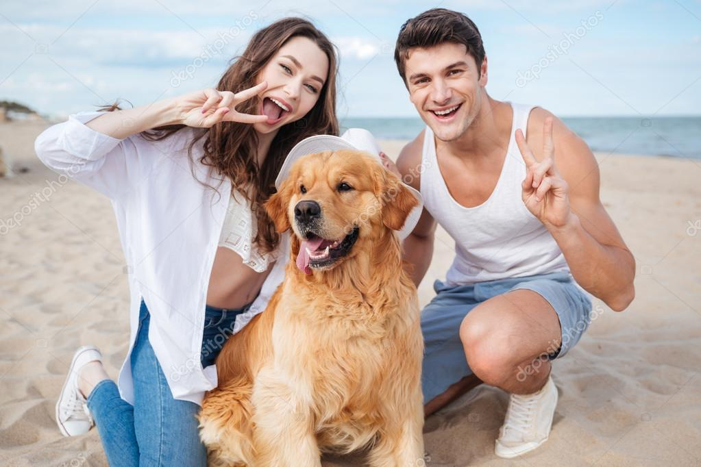 Young stylish beautiful couple in love sitting playing with dog