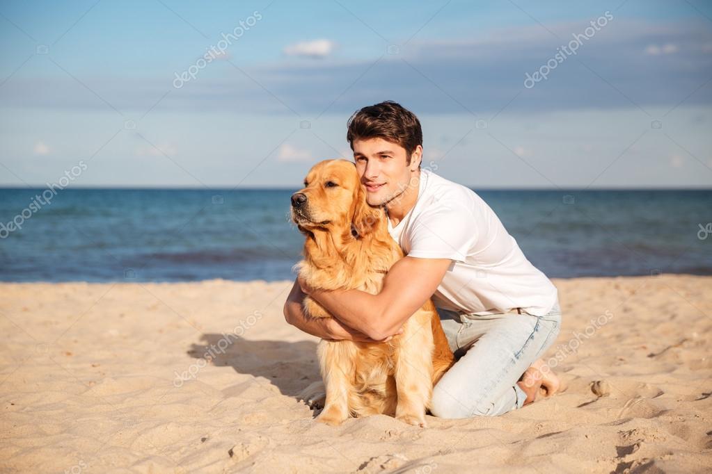 Y Hombre En Su La Playa Sentado — Fotos De Stock Abrazando Perro A A34RjL5