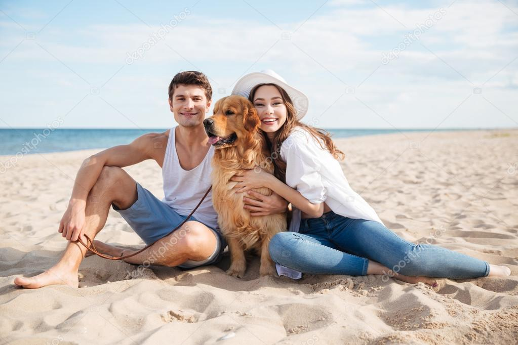 Young smiling couple in love sitting on beach with dog
