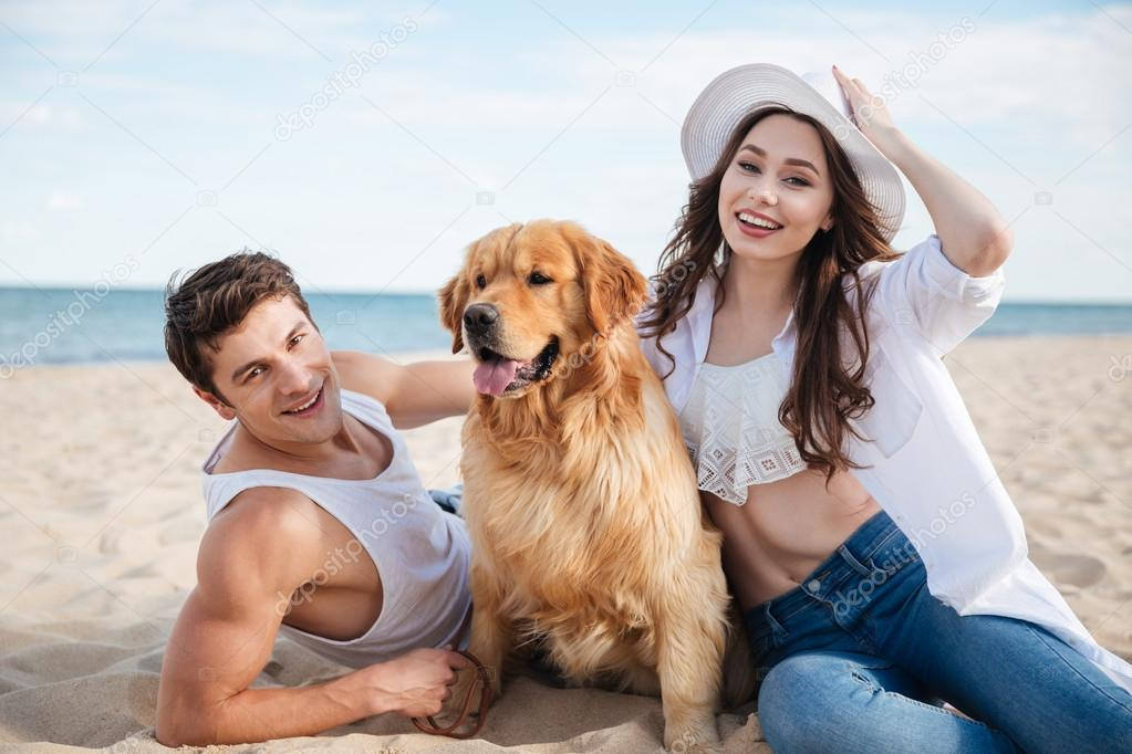 Happy smiling couple in love sitting on beach with dog