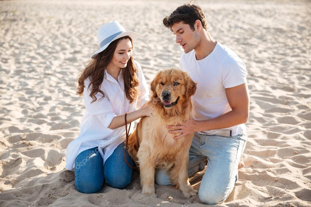 Couple spending time on the beach with their dog