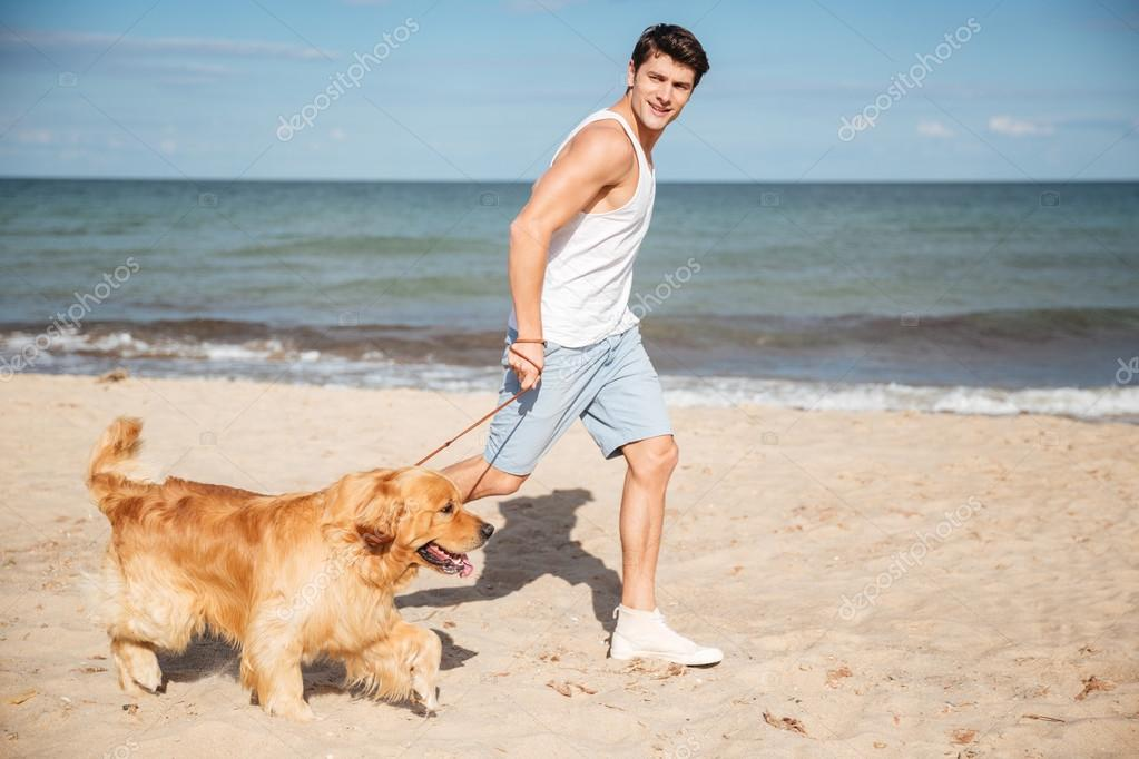 Man jogging and having fun with dog on the beach