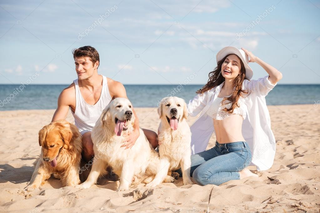 Couple with three dogs sitting on the beach