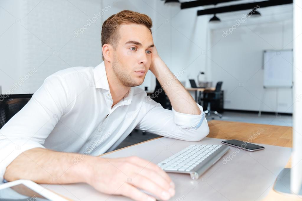 sad bored young businessman working with computer in office stock