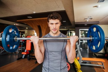 Attracitve young sportsman training using barbell in gym