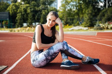 Fitness young woman resting on running track