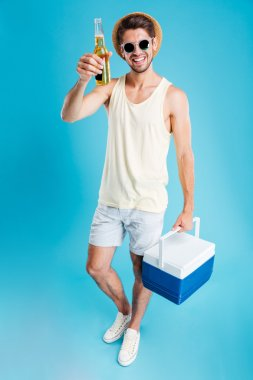 Smiling young man holding cooler bag and drinking beer