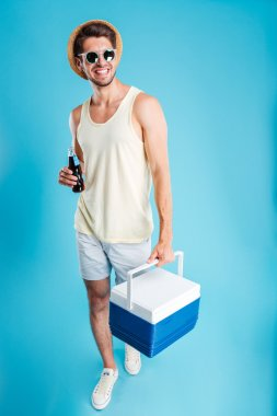 Man with bottle of soda walking and holding cooling bag