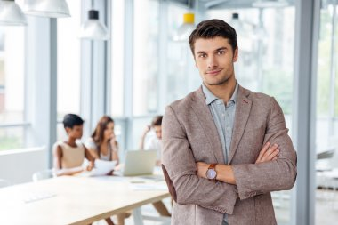 Successful businessman standing with arms crossed in office