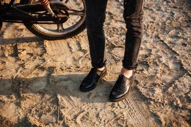 Cropped image of men legs standing near motorbike