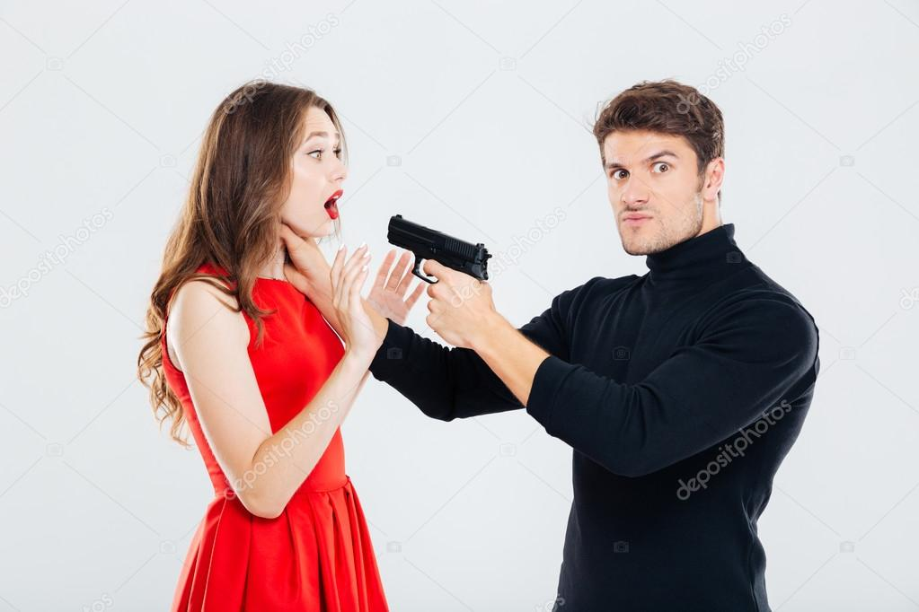 Angry man choking and threatening with gun to woman ...