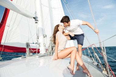 Young beautiful married couple kissing on the yacht