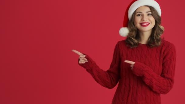 Atraktivní žena na sobě teplý červený svetr a vánoční klobouk ukazuje na stranu s oběma rukama stojí izolované přes červené pozadí