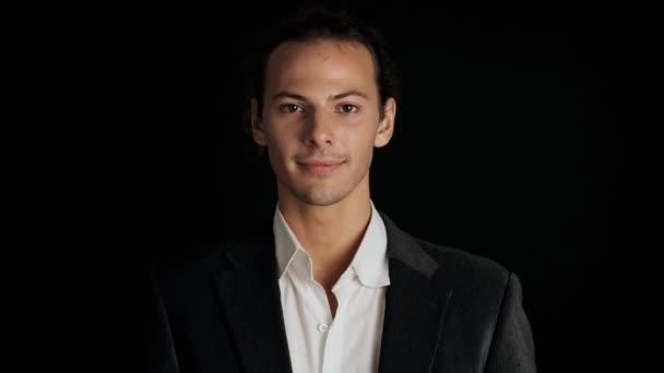 Mladý překvapený pozitivní muž v obleku izolované přes černé pozadí