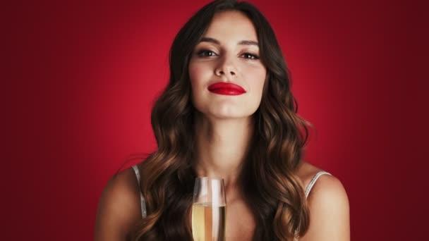 Eine Nahaufnahme einer schönen Frau posiert für die Kamera, während sie ein Glas Champagner isoliert vor rotem Hintergrund im Studio hält.