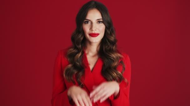 Eine überraschte Frau im roten Blazer öffnet ihren Mund, steht isoliert vor rotem Hintergrund im Studio