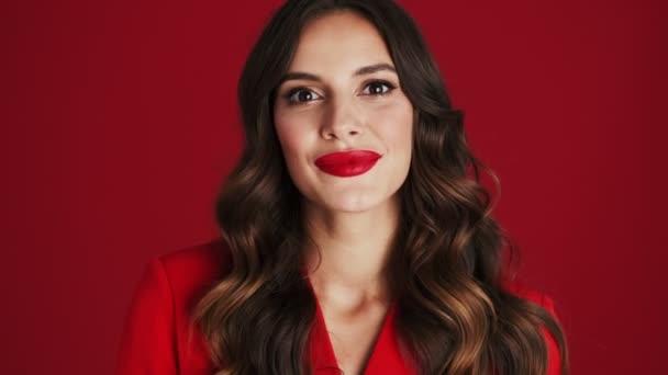 Nahaufnahme einer überraschten Frau im roten Blazer steht isoliert über rotem Hintergrund im Studio