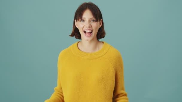 Egy boldog nő nevet, elszigetelten áll egy kék háttérben a stúdióban.