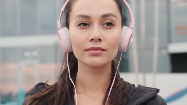 Mladý úžasný sportovní žena poslech hudby s sluchátky venku na pláži