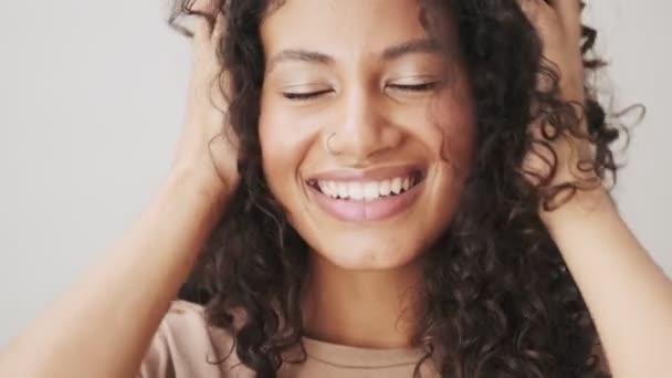 Detailní záběr šťastné africké Američanky pózuje na kameru stojící izolovaně nad béžovým pozadím