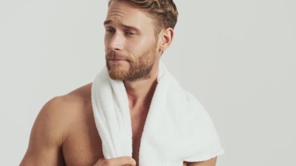 Usmívající se polonahý blonďák s ručníkem na ramenou pózuje izolovaně nad šedým pozadím ve studiu