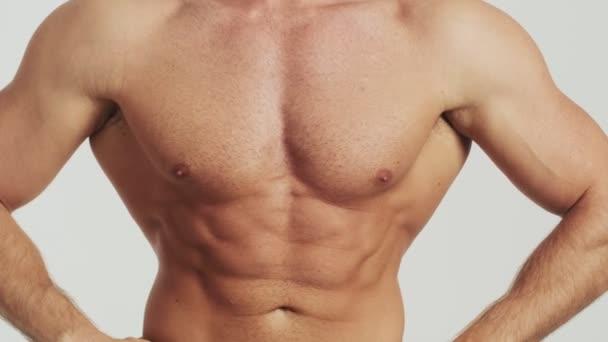 Pohled na polonahého muže ukazuje svaly trupu kameře, která stojí izolovaně nad šedým pozadím ve studiu.